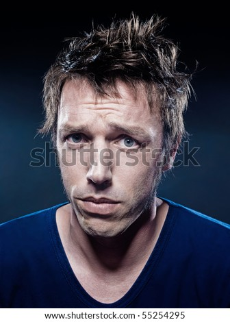 studio portrait on black background of a funny expressive caucasian man puckering sad - stock photo