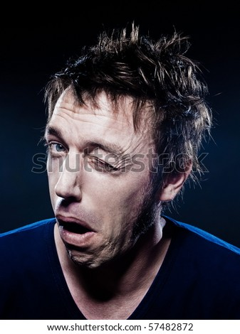 studio portrait on black background of a funny expressive caucasian man winking - stock photo