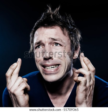 studio portrait on black background of a funny expressive caucasian man with crossed fingers hoping lucky