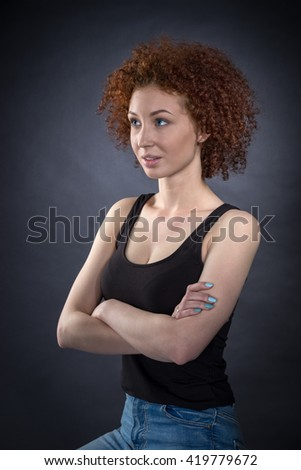 studio portrait on dark background pretty red-haired girl with arms crossed
