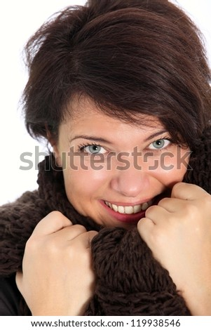 Studio portrait over white of a smiling brunette woman snuggling up in a winter, knitted scarf - stock photo