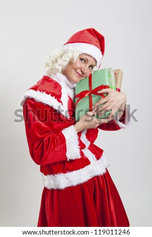 Studio portrait shot of happy Santa Claus helper elf holding Christmas presents