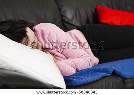 Studio shoot of a beautiful young woman resting on the black leather couch on top of a blue woven blanket. Her head is resting on a white pillow. - stock photo