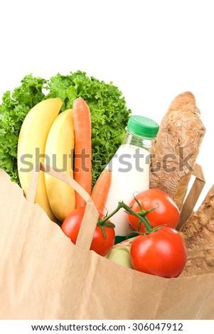 Studio shoot of paper shopping bag with bread, green salad, tomato, bananas, milk, carot on white background