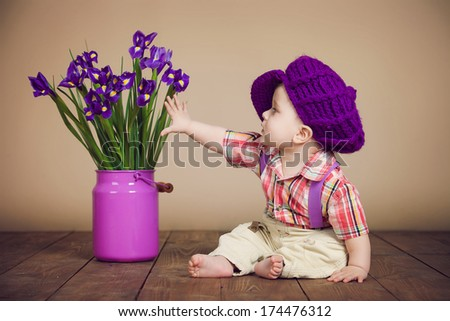 Studio shot a happy-looking baby posing for the camera with flowers in jug - stock photo