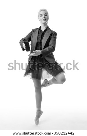 Studio shot af a ballerina model wearing a suit jacket holding a mobile phone - stock photo