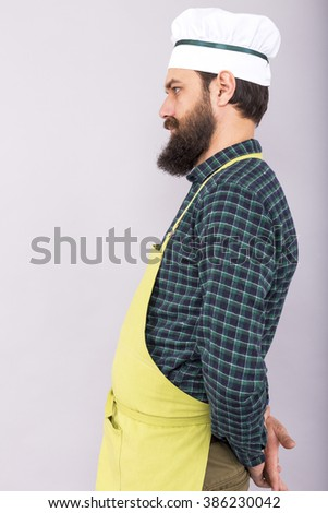 Studio shot of a bearded man with apron and cook hat over gray background - stock photo