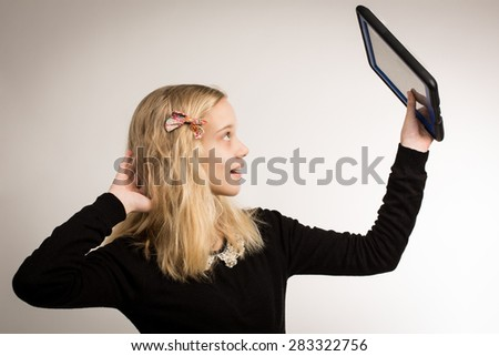 Studio shot of a beautiful blond teenage girl with long hair wearing a bow and a black top taking a selfie. - stock photo