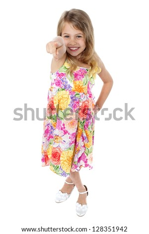 Studio shot of a beautiful girl in floral designed frock pointing towards you. - stock photo