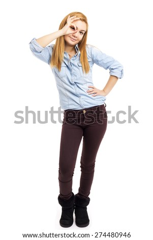 Studio shot of a beautiful girl  looking through ok sign and smiling over white background - stock photo