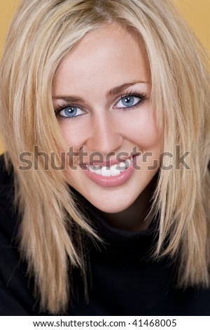 Studio shot of a beautiful happy blond haired blue eyed woman with perfect teeth and smile