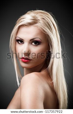 Studio shot of a beautiful topless blond woman on gray background, closeup - stock photo