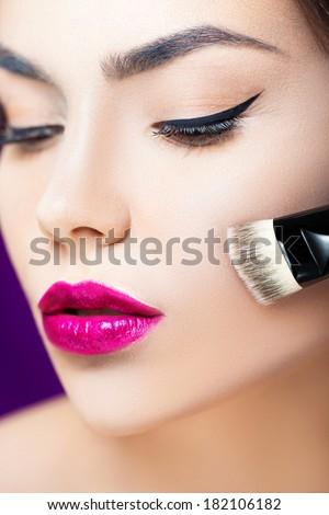 Studio shot of a beautiful woman applying foundation - stock photo