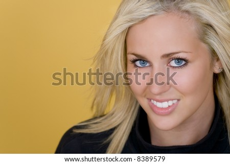 Studio shot of a beautiful young blond woman with bright blue eyes looking happy