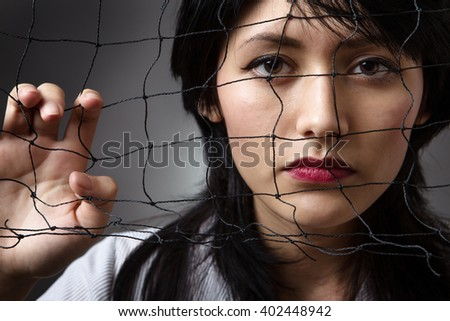 Studio shot of a business woman behind a  net