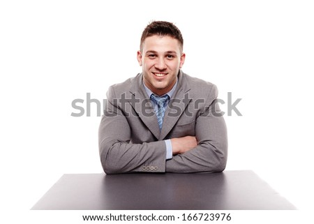 Studio shot of a cheerful businessman sitting at a table with arms folded, isolated over white background - stock photo
