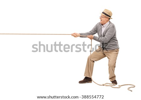 Studio shot of a cheerful senior pulling a rope isolated on white background - stock photo