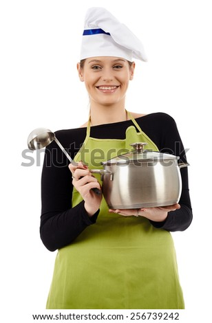 Studio shot of a cheerful woman cook holding a pot and a soup ladle isolated on white background - stock photo