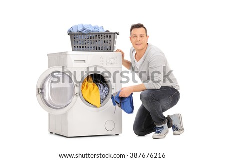 Studio shot of a cheerful young man doing laundry and looking at the camera isolated on white background - stock photo