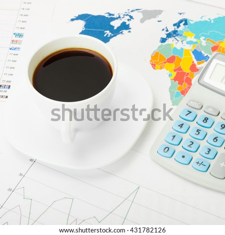 Studio shot of a coffee cup and calculator over world map and some documents