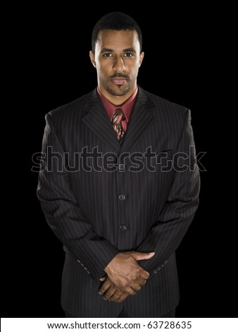 Studio shot of a confident African American businessman with clasped hands looking intensely directly into the camera against a black background. - stock photo