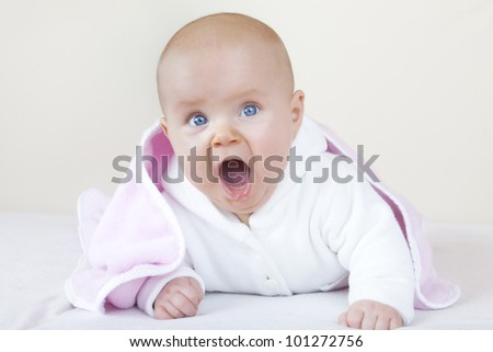 studio-shot of a cute baby girl on bed learning how to crawl.