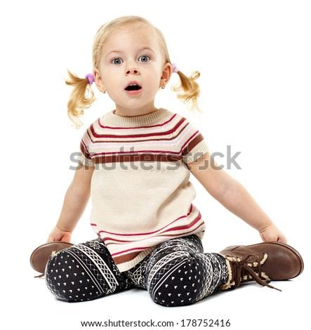 Studio shot of a cute toddler girl sitting on the floor and expressing surprise isolated over white background - stock photo