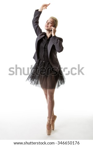 Studio shot of a dancer wearing a tutu and a suit jacket, holding a mobile phone - stock photo
