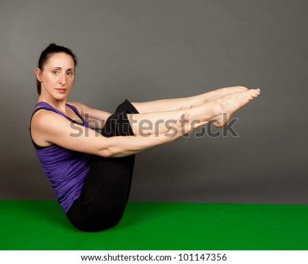 Studio shot of a fit brunette woman in a paripurna boat pose on a grey background