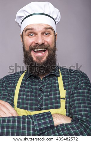 Studio shot of a funny bearded man with cook hat holding arms crossed over gray background - stock photo