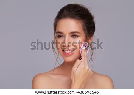 Studio shot of a gorgeous girl applying face powder - stock photo