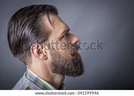 Studio shot of a handsome young man with retro look, beard and mustache - stock photo
