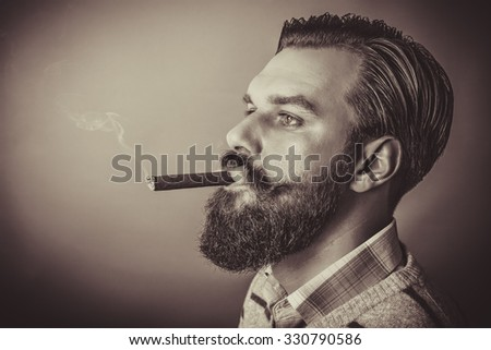 Studio shot of a handsome young man with retro look smoking a cigar - stock photo