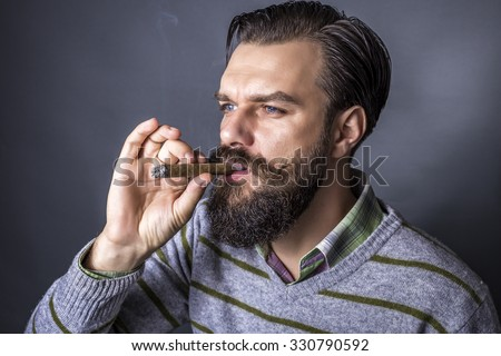 Studio shot of a handsome young man with retro look smoking a cigar over gray background - stock photo