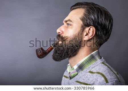 Studio shot of a handsome young man with retro look smoking pipe over gray background - stock photo