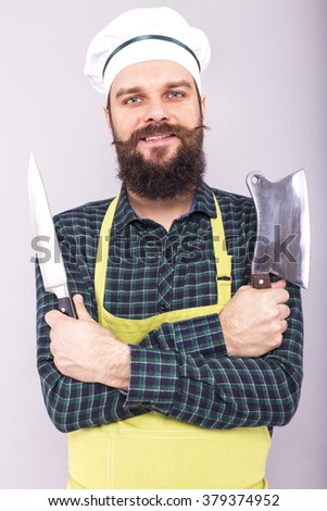 Studio shot of a happy bearded young man holding sharp knives over gray background