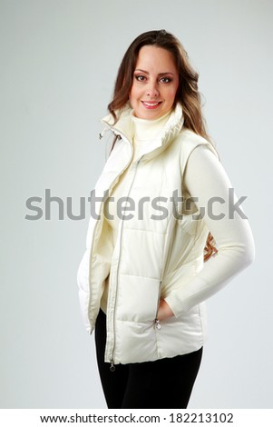 Studio shot of a happy woman standing over gray background - stock photo