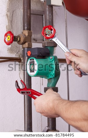 studio-shot of a heating engineer repairing and maintaining the heating system of a single-family house.