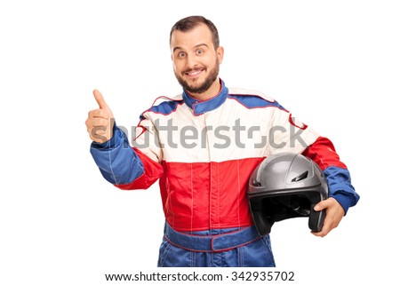 Studio shot of a joyful car racer in a racing uniform holding a helmet and giving a thumb up isolated on white background - stock photo