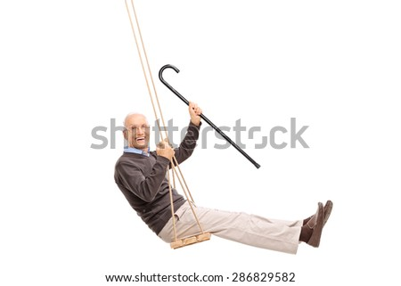 Studio shot of a joyful senior swinging on a swing and holding a cane isolated on white background - stock photo