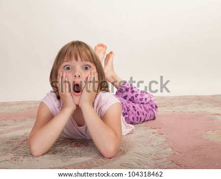 Studio shot of a little girl lying on a carpet with a surprised look.