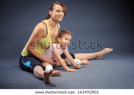 Studio shot of a little girl with mother at fitness exercise - stock photo