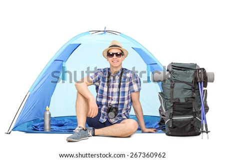 Studio shot of a male camper sitting in front of a blue tent with a backpack beside him isolated on white background - stock photo