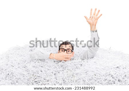 Studio shot of a man drowning in a pile of shredded paper isolated on white background - stock photo