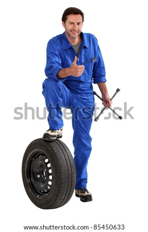 Studio shot of a mechanic with tyre and wrench, giving a thumbs up - stock photo