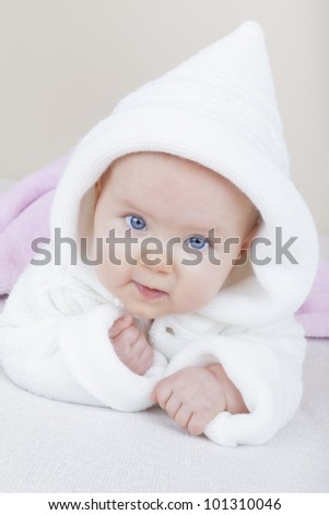 studio-shot of a 6 month old baby girl lying on bed and learning how to crawl. - stock photo