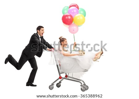 Studio shot of a newlywed couple driving in a shopping cart isolated on white background