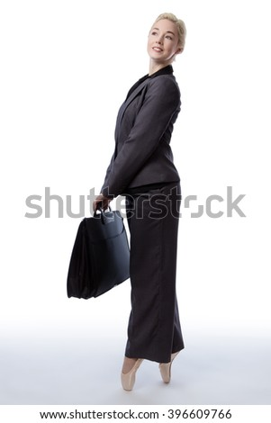 Studio shot of a pretty blonde business model, wearing a suit and ballet shoes, is enpointe whilst holding a briefcase, isolated on a white background.
