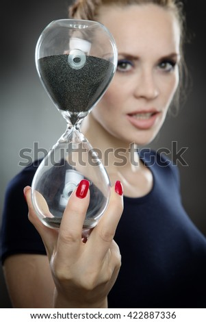 Studio shot of a pretty business model holding a large sandtimer watching the sand of time run out.  Shot on a grey background - stock photo