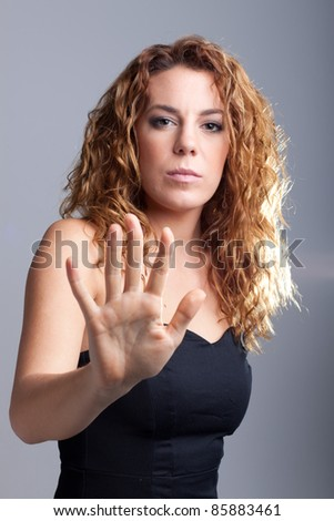 studio shot of a redhead girl making a stop sign with her hand